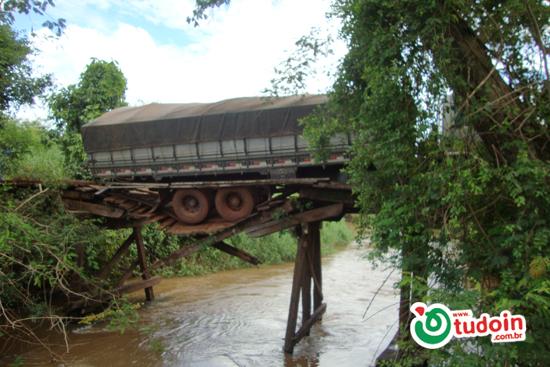 Caminhão carregado de laranja quebra ponte e quase cai em córrego